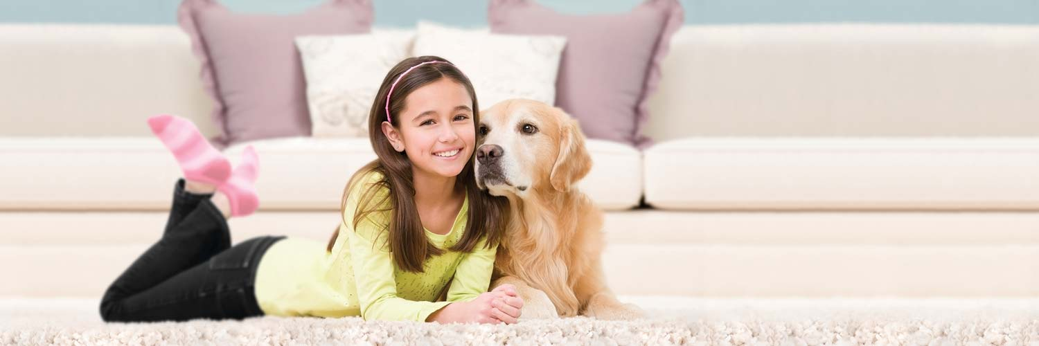 young girl and a dog sitting on a rug